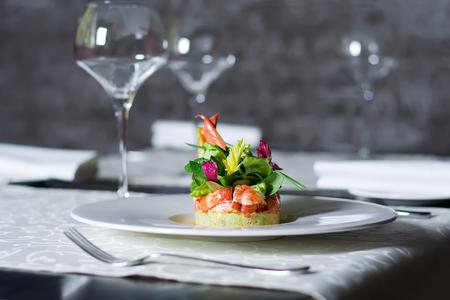 Exclusief eten, haute cuisine geserveerd in restaurant interieur. Kreeftvlees voorgerecht op wit bord. Zeevruchten delicatesse