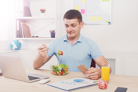 eating right: Man surprised of his healthy business lunch in modern office. Young handsome businessman in casual at working place, look at fork displeased with vegetable salad bowl, diet and eating right concept. Stock Photo