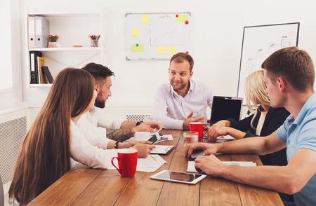 Zakelijke bijeenkomst. Jonge gelukkige glimlachende zakenlieden en vrouwen op modern kantoor, team collectieve bespreking met tablet op het werk. Brainstormen, plannen en communiceren met partners voor het opstarten