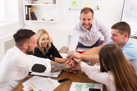 teambuilding: Team put hands together, show connection and alliance. Teambuilding in the office, young businessmen and women in casual unite hands for teamwork and cooperation at new project.