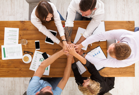 Team put hands together, show connection and alliance. Teambuilding in the office, young businessmen and women in casual unite hands for teamwork and cooperation at project. Top view, overhead