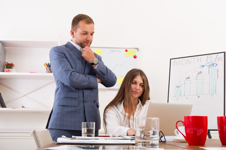 Businessman supervising his assistant's work on the laptop computer. Man helps woman in the office. Male boss and female secretary. Communication of manager and staff, checking job execution
