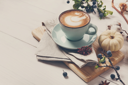 Pumpkin spice latte. Blue coffee cup with creamy foam on desk, autumn dried flowers, sloe and small yellow pumpkins at white wood background. Fall hot drinks, seasonal offer concept