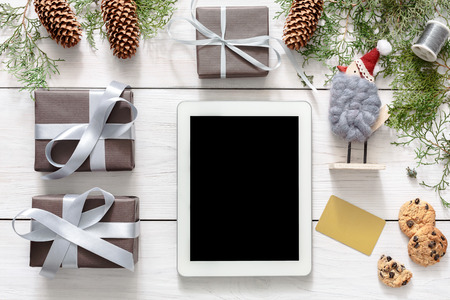 fiestas electronicas: Christmas online shopping background. Tablet screen with copy space top view on white wood, present boxes and cookies. Electronic devices, internet commerce on winter holidays concept Foto de archivo
