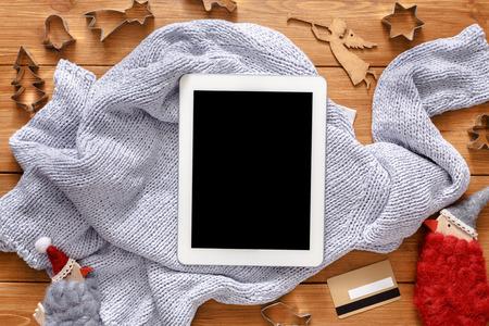fiestas electronicas: fondo línea de las compras de Navidad. pantalla de la tablet con espacio de copia vista desde arriba en la madera, tarjeta de crédito y suéter caliente. dispositivos electrónicos, el comercio por Internet en vacaciones de invierno concepto Foto de archivo