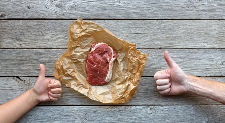 show of hands: Raw beef steak in craft paper on dark wooden table background, top view with two hands show thumb up. Fresh juicy meat food. Cooking ingredients, butchers and grocery concept