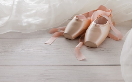 pointe shoes: Pastel pink ballet shoes background. New pointe shoes with satin ribbon and chiffon tutu lay on white rustic shubby chic wood, copy space