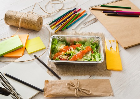 eat right: Healthy lunch of artist. Diet concept. Take away food in foil boxes, papers and pencils on working table of creative person or art student. Salmon salad on white wood Stock Photo