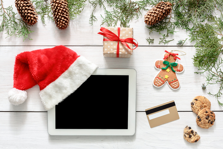 fiestas electronicas: Christmas online shopping background. Tablet screen with copy space top view on white wood, credit card, present boxes and santa hat. Electronic devices, internet commerce on winter holidays concept
