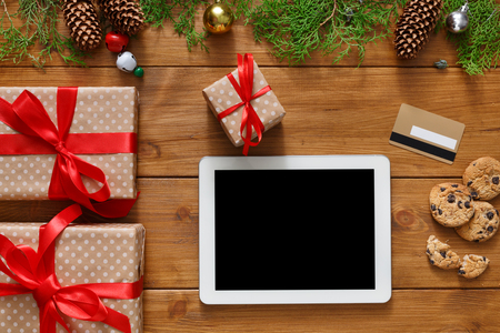 fiestas electronicas: Christmas online shopping background. Tablet screen with copy space top view on wood, credit card and present boxes. Electronic devices, internet commerce on winter holidays concept