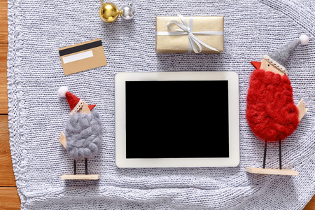 fiestas electronicas: Christmas online shopping background. Tablet screen with copy space top view on warm knitted sweater cloth, present box and credit card. Electronic device, internet sales on winter holidays concept