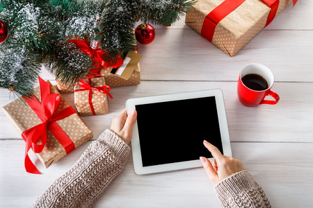 Christmas online shopping top view on wood. Female buyer touch screen of tablet, copy space. Woman has coffee, buys presents near xmas tree, among gift boxes. Winter holidays sales background Banco de Imagens - 65667437