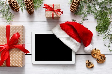 fiestas electronicas: Christmas online shopping background. Tablet screen with copy space top view on white wood, present boxes, santa hat and cookies. Electronic devices, internet commerce on winter holidays concept