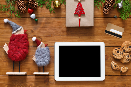 fiestas electronicas: Christmas online shopping background. Tablet screen with copy space top view on wood, credit card, xmas toys ans presents. Electronic devices, internet commerce on winter holidays concept