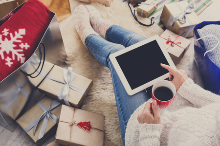 Christmas online shopping top view. Female buyer click at screen of tablet, make internet order with credit card. Woman buy presents for xmas eve, among gift boxes and packages. Winter holidays sales Banco de Imagens - 65850526