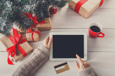 indoor background: Christmas online shopping above view on wood. Female buyer touch screen of tablet, copy space. Woman has coffee, buys presents near christmas tree, among gift boxes. Winter holidays sales background Stock Photo