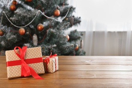 indoor background: Wrapped present boxes decorated with red ribbon on table closeup and beautiful decorated christmas tree with ornaments and garland unfocused. Winter holiday gifts background