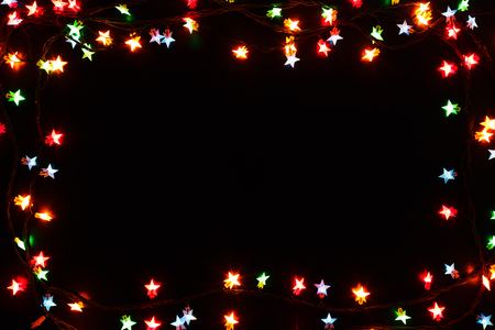 christmas lights stars frame on black background holiday shiny garland border with copy space