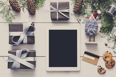 fiestas electronicas: fondo línea de las compras de Navidad. pantalla de la tablet con espacio de copia vista desde arriba en madera blanca, cajas de autos, tarjetas de crédito y las galletas. dispositivos electrónicos, el comercio por Internet en vacaciones de invierno concepto Foto de archivo