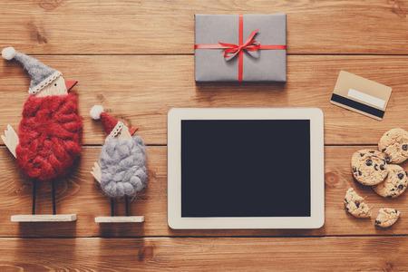 fiestas electronicas: fondo línea de las compras de Navidad. pantalla de la tablet con espacio de copia vista desde arriba en la madera, tarjeta de crédito, los juguetes de Navidad y regalos. dispositivos electrónicos, el comercio por Internet en vacaciones de invierno concepto Foto de archivo