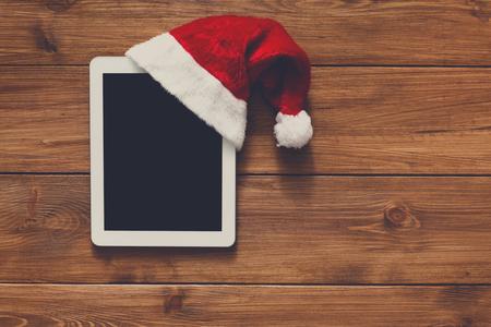 fiestas electronicas: fondo línea de las compras de Navidad. pantalla de la tablet en santa visión sombrero de copa en la madera con espacio de copia. dispositivos electrónicos, el comercio por Internet en vacaciones de invierno concepto