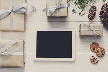 fiestas electronicas: fondo línea de las compras de Navidad. pantalla de la tablet con espacio de copia vista desde arriba en madera blanca, cuadros presentes y las galletas. dispositivos electrónicos, el comercio por Internet en vacaciones de invierno concepto