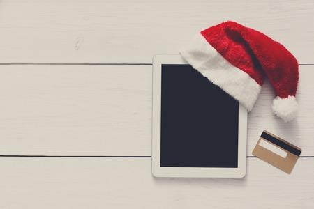 fiestas electronicas: fondo línea de las compras de Navidad. pantalla de la tablet en santa sombrero vista superior sobre madera blanca con copia espacio y la tarjeta de crédito de oro cerca. dispositivos electrónicos, el comercio por Internet en vacaciones de invierno concepto