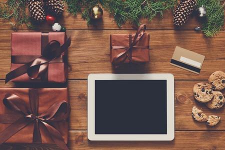 fiestas electronicas: fondo línea de las compras de Navidad. pantalla de la tablet con espacio de copia vista desde arriba en la madera, tarjeta de crédito y cajas presentes. dispositivos electrónicos, el comercio por Internet en vacaciones de invierno concepto