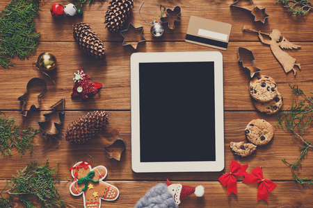 fiestas electronicas: Christmas online shopping background. Tablet screen with copy space top view on wood, credit card and handmade gingerbread set. Electronic devices, internet commerce on winter holidays concept Foto de archivo