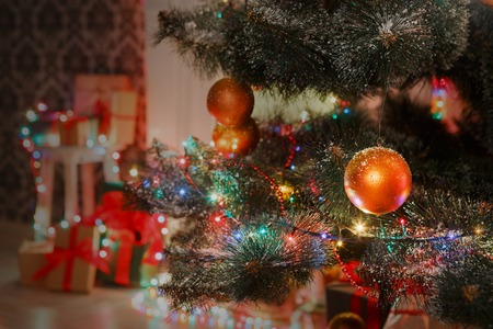 christmas baubles of modern design: Christmas magic. Beautiful decorated xmas tree closeup in modern living room. Shining lights, baubles, balls and garland. Winter holiday night, magic atmosphere. Design and decorations background