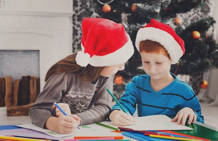 Writing letter to santa. Adorable children in santa hats make wish list of presents for christmas. Waiting for gift. Prepare for winter holidays. Boy and girl, brother and sister in decorated room