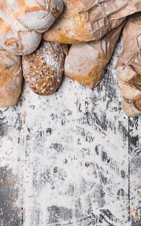 sorts: Baking and cooking concept background. Border of different bread sorts, wrapped in craft paper top view with copy space on wooden table, sprinkled with flour, vertical Stock Photo