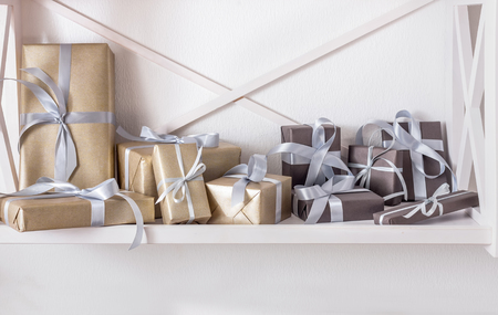 high key: Elegant gift boxes wrapped in paper on white shelves in modern interior. Any holiday background with copy space. Christmas, birthday or valentine concept. High key