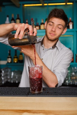 vertical bar: Young handsome barman in bar interior pouring red alcohol to cocktail drink from shaker. Professional bartender at work in night club. Service industry occupation. Vertical image Stock Photo