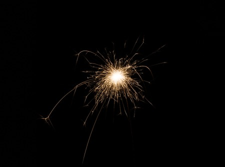 New year party burning sparkler on black background. Glowing holiday sparkling hand fireworks, shining fire flame. Christmas light. Stock Photo