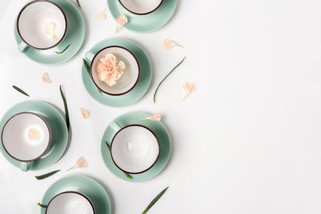 Sauberes Geschirr, Kaffee oder Tee-Set. Zusammensetzung der eleganten Porzellantassen und Untertassen mit Blütenblättern und Kopie Platz auf weißem Hintergrund, High Key, Ansicht von oben und flach lag.