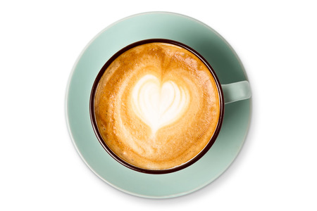 Cappuccino with frothy foam heart shape, blue coffee cup top view closeup isolated on white background. Cafe and bar, barista art concept. Stock Photo