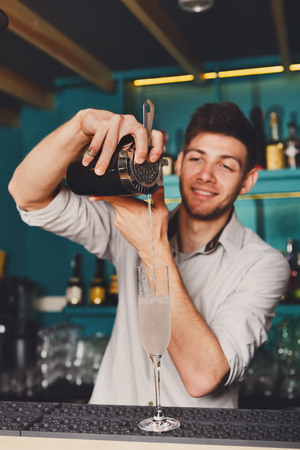 Young handsome barman in bar interior pouring alcohol cocktail drink into glass. Professional bartender at work in night club. Service industry occupation. Vertical image Stock Photo