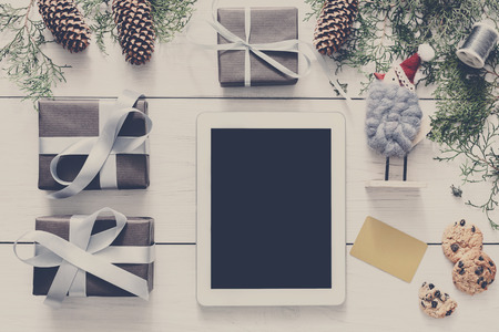 fiestas electronicas: Christmas online shopping background. Tablet screen with copy space top view on white wood, present boxes, credit card and cookies. Electronic devices, internet commerce on winter holidays concept
