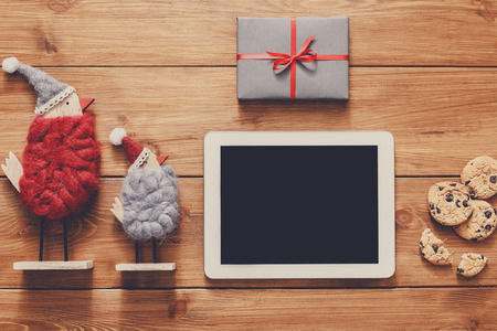fiestas electronicas: Christmas online shopping background. Tablet screen with copy space top view on wood, credit card, xmas toys and presents. Electronic devices, internet commerce on winter holidays concept