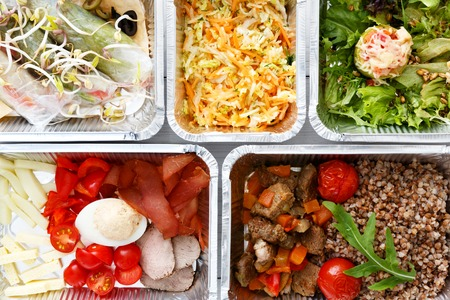 kasha: Healthy food background. Take away of natural organic meals in foil boxes. Fitness nutrition, eggs, meat, fresh vegetables and kasha buckwheat porridge. Top view, flat lay. Restaurant dishes delivery