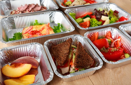 Healthy eating, diet concept. Take away organic food. Weight loss nutrition in foil boxes. Vegetable salads, peach fruits and whole grain sandwiches with cheese at white wood Stock fotó
