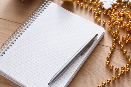 wishlist: Christmas planning background. Prepare to winter holidays. Top view flat lay of xmas decorations, note papers, pen and mobile phone on wood. Copy space for wishlist or shedule Stock Photo