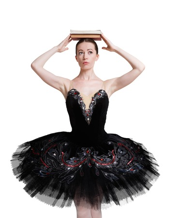 animal tutu: Graceful ballerina making exercise for training ballet posture against white background, isolated. Professional dancer in black tutu skirt with books pile on head. Choreography classes concept