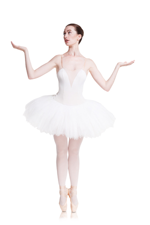 Classical Ballet dancer. Beautiful graceful ballerine practice ballet positions in tutu skirt, holds something with open hands. Place for anything, full-length portrait isolated on white background