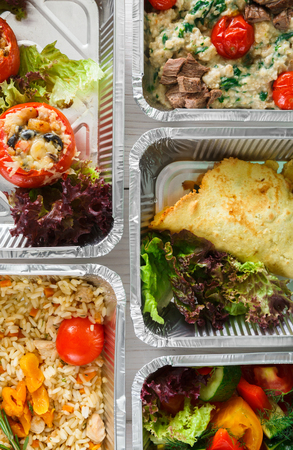 Healthy food background. Take away of natural organic meals in foil boxes. Fitness nutrition, meat, fresh vegetable salads and eggs. Top view, flat lay. Restaurant dishes delivery