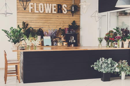 Small business. Modern flower shop interior. Floral design studio, decorations and arrangements. Flowers delivery service and sale of home plants in pots, wooden showcase, filtered image Banco de Imagens