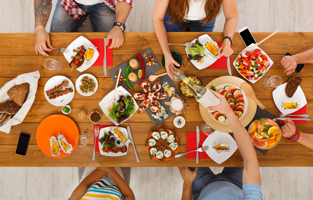 People eat healthy meals at served festive table served for party. Friends celebrate with organic food on wooden table top view. Drink wine and have fun together Stock Photo
