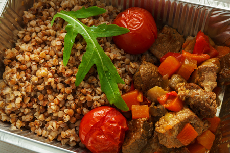kasha: Healthy food in foil box closeup. Russian kasha buckwheat porridge with dried tomatoes and beef stew. Restaurant dishes delivery, lunch for diet