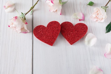 Valentine background with pink rose flowers petals and handmade wooden glitter hearts on white rustic wood. Happy lovers day mockup, copy space Stock Photo